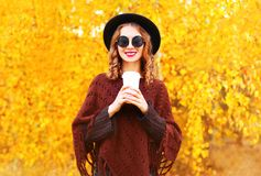 Fashion autumn woman holds coffee cup in black round hat. Knitted poncho on a yellow leaves background stock images