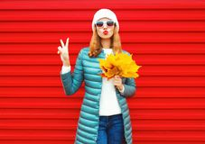 Fashion autumn woman holds yellow maple leaves, blows red lips. Sends an air kiss on background in city stock photography