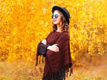 Fashion autumn woman wearing a black round hat and knitted poncho. On a yellow leaves background stock image