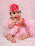 Fashion baby. Little hispanic girl sitting and dressed in pink with sunglasses and flower hat Stock Images