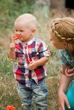 Fashion baby boy and his mother smelling flower Stock Image