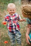 Fashion baby boy and his mother smelling flower. Fashion baby boy wearing checkered shirt and his mother smelling flower Stock Photography