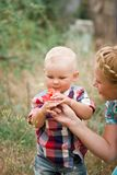 Fashion baby boy and his mother smelling flower. Fashion baby boy wearing checkered shirt and his mother smelling flower Stock Image