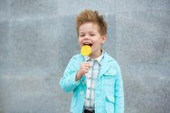 Fashion kid with lollipop near gray wall Stock Photography