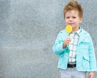 Fashion kid with lollipop near gray wall stock photos