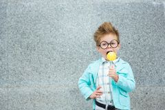 Fashion kid with lollipop near gray wall. Fashion baby boy in mint jacket stands on a gray wall background. Trendy boy with lollipop standing on the street royalty free stock images