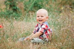 Fashion baby boy walking in grass. Fashion baby boy wearing checkered shirt walking in grass Royalty Free Stock Photo