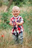 Fashion baby boy walking in grass. Fashion baby boy wearing checkered shirt walking in grass Royalty Free Stock Photography