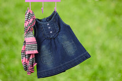 Fashion baby dresses hanging on a hanger on a green  background Royalty Free Stock Photos