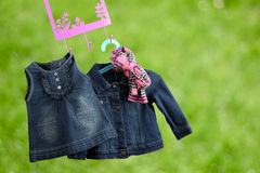 Fashion baby dresses hanging on a hanger on a green  background Royalty Free Stock Image