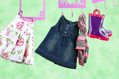 Fashion baby dresses hanging on a hanger on a green  background Royalty Free Stock Images