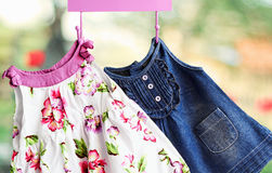 Fashion baby dresses. Hanging on a hanger on a green summer background stock photo