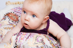 Fashion baby girl lying. On a beautiful fabric in the basket and looks to the side on a white background stock photos