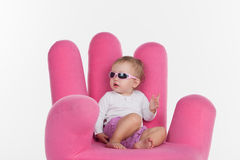 Fashion baby girl sitting at pink chair in form of hand. Royalty Free Stock Images
