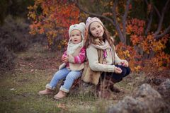 Fashion baby girls sisters stylish dressed brunnette and blond wearing warm autumn clothes jackets posing happy together in colour. Ful forest foliage.Face with Royalty Free Stock Photography