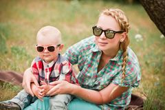 Fashion baby in sunglasses sitting with mother under the tree. Fashion baby wearing sunglasses and checkered shirt sitting with mother under the tree Stock Photos