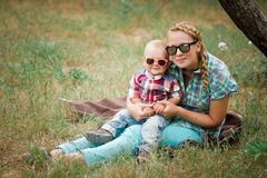 Fashion baby in sunglasses sitting with mother under the tree. Fashion baby wearing sunglasses and checkered shirt sitting with mother under the tree Royalty Free Stock Images