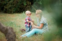 Fashion baby in sunglasses sitting with mother under the tree. Fashion baby wearing sunglasses and checkered shirt sitting with mother under the tree Stock Image