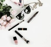 Fashion background. Female fashionable stylish accessories .Bouwuet of pale pink roses. Bag, sunglasses and cosmetics on a white background. Copy space.Flat stock photo
