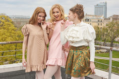Fashion ballerinas in colourful dresses want to taste a sweet macaroons Royalty Free Stock Image