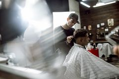 The fashion barber in black clothes makes a razor cut hair for a black-haired man sitting in the armchair in a royalty free stock photography