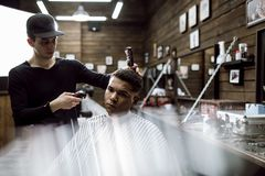 The fashion barber in black clothes makes a razor cut hair for a black-haired man sitting in the armchair in a stock photo