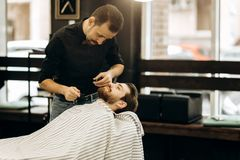 Fashion barber with mustache dressed in a black shirt with a red bow tie trims men`s beard in the barbershop royalty free stock images