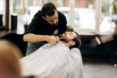 Fashion barber with mustache dressed in a black shirt with a red bow tie trims men`s beard in the barbershop stock photography