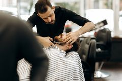 Fashion barber with mustache dressed in a black shirt with a red bow tie trims men`s beard in the barbershop stock photos
