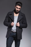 Fashion bearded man holding his long coat Stock Photos