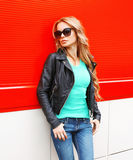 Fashion beautiful blonde woman in sunglasses black rock jacket at city over red. Background Royalty Free Stock Photos