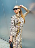 Fashion beautiful blonde woman wearing a leopard dress and sunglasses with handbag clutch Stock Photography