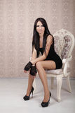 Fashion Beautiful Brunette Girl Model posing on luxury chair in Stock Photo