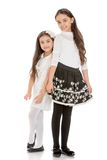 Fashion beautiful, charming girls sisters in. Beautiful black-and-white outfits - on white background Royalty Free Stock Photo