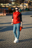 Fashion beautiful girl with collected hair looks. She is wearing a red vest and jeans, his shoulder red fashion handbag stock photos