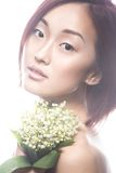 Fashion beautiful girl oriental type with delicate natural make-up and flowers. Beauty face. Stock Photos
