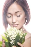 Fashion beautiful girl oriental type with delicate natural make-up and flowers. Beauty face. Stock Image