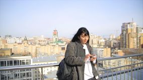 Fashion beautiful hispanic latina woman texting on smartphone in the city drinking latte coffee. Rooftop with cityview at background stock video