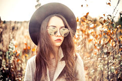 Fashion beautiful lady in autumn landscape. Outdoor fashion photo of young beautiful lady in autumn landscape with dry flowers. Gray coat, black hat, sunglusses Royalty Free Stock Photo