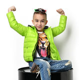 Fashion beautiful little boy in green winter clothing jacket sit Stock Image