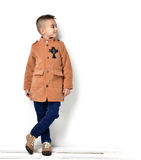 Fashion beautiful little boy in orange brown clothing jacket and Royalty Free Stock Photography