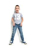 Fashion beautiful little boy in t-shirt jeans standing and happy Royalty Free Stock Images