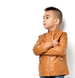 Fashion beautiful little boy in yellow winter brown leather clot. Hing jacket standing and looking at the corner over white background Stock Photos