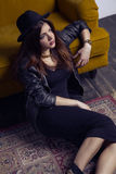Fashion beautiful middle eastern model with hipster style is posing on carpet and yellow sofa. Royalty Free Stock Images