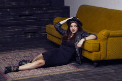 Fashion beautiful middle eastern model with hipster style is posing on carpet and yellow sofa. Royalty Free Stock Photos