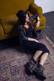 Fashion beautiful middle eastern model with hipster style is posing on carpet and yellow sofa. Stock Photo