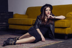 Fashion beautiful middle eastern model with hipster style is posing on carpet and yellow sofa. Stock Photography