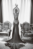 Fashion beautiful sensual woman in luxurious dress with long train, posing between two modern armchairs in front of window at int. Erior. indoor full length royalty free stock image