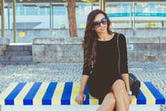 Fashion beautiful smiling. Fashion beautiful on the colored bench smiling at the camera royalty free stock image