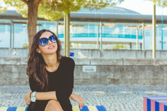 Fashion beautiful smiling. Fashion beautiful on the colored bench smiling at the camera royalty free stock photography
